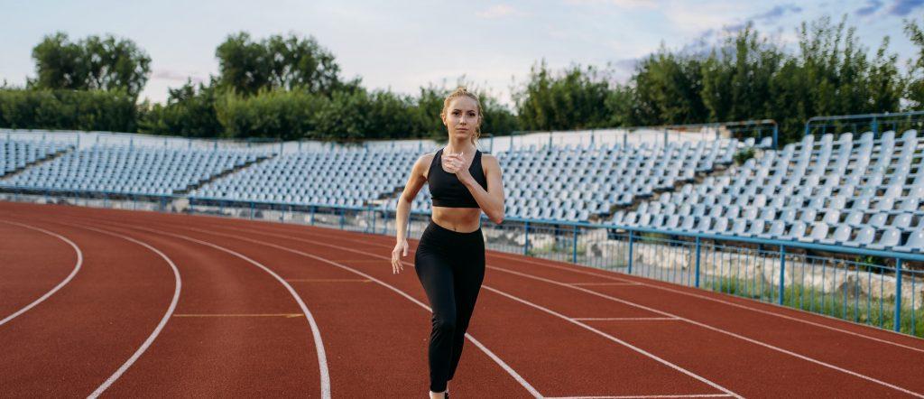 Female jogger running, training on stadium